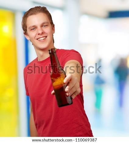 portrait of young man holding beer indoor - stock photo