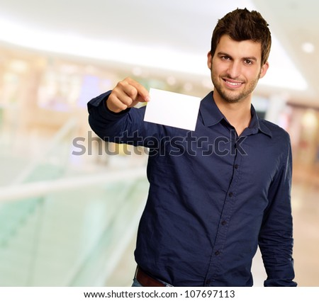 Portrait Of Young Man Holding Blank White Card, Indoor - stock photo