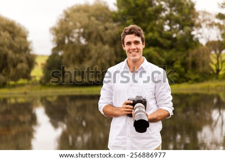 portrait of young man holding digital camera - stock photo