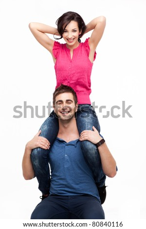 Portrait of young man holding his happy girlfriend on shoulders - stock photo
