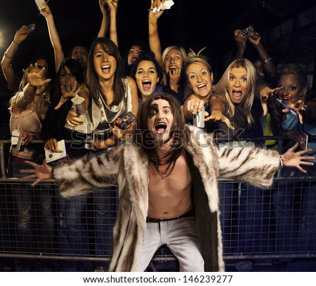 Portrait of young man in fur coat screaming with excited audience in the background - stock photo