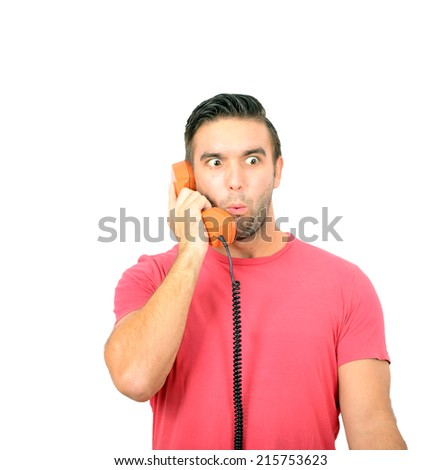 Portrait of young man in shock while talking on phone having unpleasant conversation against white background - stock photo