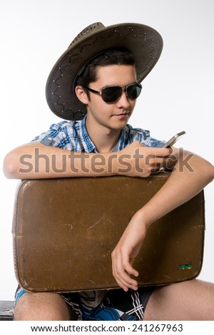 Portrait of young man in sunglasses with a suitcase. traveler in a hat with a phone in his hand. - stock photo