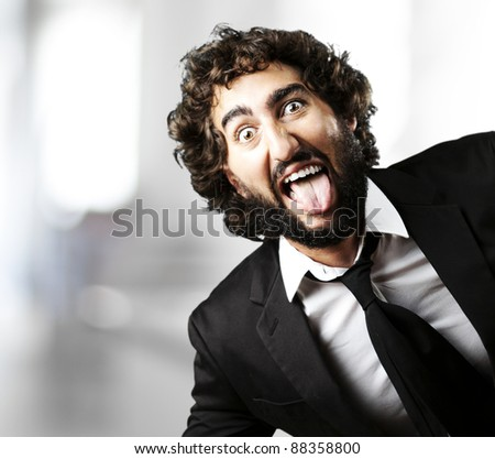 portrait of young man joking and showing the tongue against a abstract background - stock photo