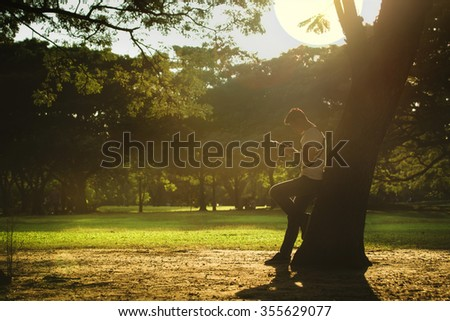 Portrait of young man leans against a tree and looking at his camera in the garden during sunset. - (Warm tone and vintage style) - stock photo