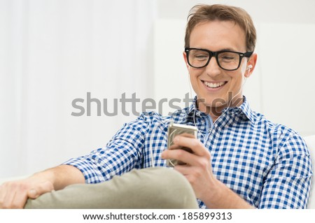Portrait Of Young Man Listening To Music With IPod - stock photo