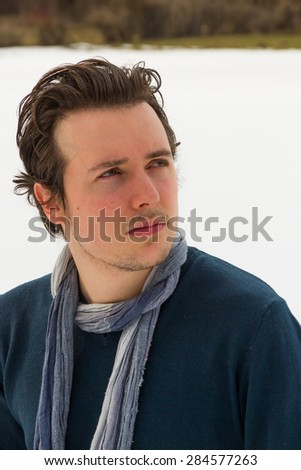 Portrait of young man looking at the top, with sweater and blue scarf around his neck and  isolated on white snow  background  - stock photo