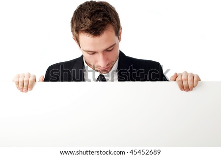 Portrait of young man looking down at blank sign. Isolated on white. - stock photo