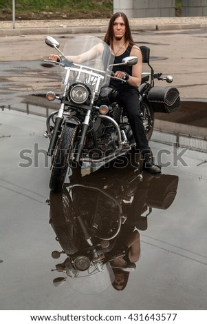 Portrait of young man on black motorcycle with puddle reflection - stock photo