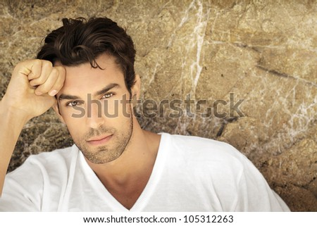 Portrait of young man outdoors with very handsome face in white casual shirt against natural background - stock photo