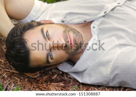 Portrait of young man outdoors with very handsome face in white casual shirt relaxing outdoors - stock photo
