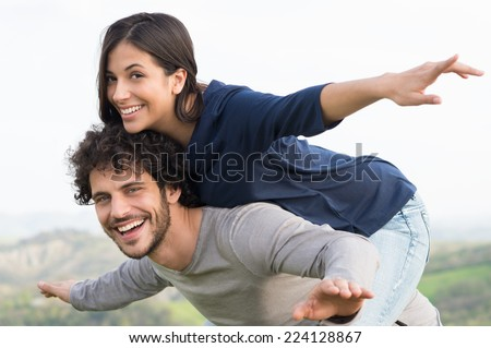 Portrait Of Young Man Piggybacking His Girlfriend Outdoor - stock photo
