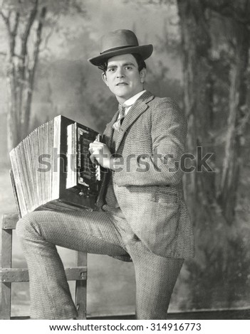 Portrait of young man playing accordion - stock photo