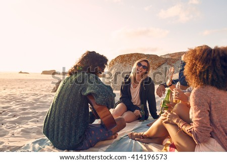 Portrait of young man playing guitar for friends. Group of friends having fun at the beach party. Young men and women sitting on the beach dinking beer. - stock photo