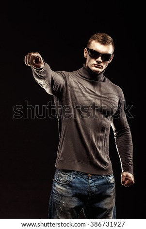 Portrait Of Young Man Points A Finger Isolated On Black Background - stock photo