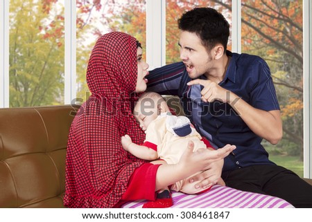 Portrait of young man scolding his wife at home while holding a baby, shot with autumn background on the window - stock photo