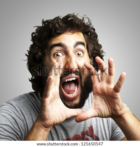 portrait of young man screaming against a grey background - stock photo
