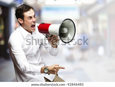portrait of young man screaming with megaphone against a crowded place - stock photo