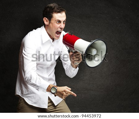 portrait of young man screaming with megaphone against a grunge wall - stock photo