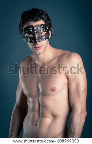 Portrait of young man shirtless with carnival mask against dark background. - stock photo