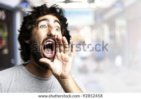 portrait of young man shouting against a crowded place - stock photo