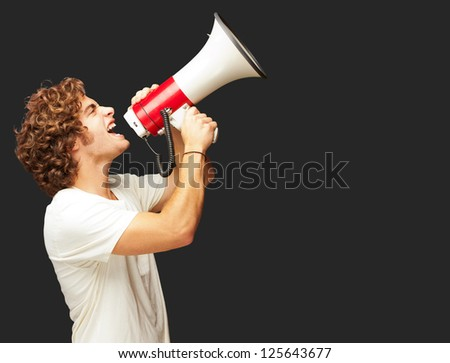 Portrait Of Young Man Shouting With A Megaphone Isolated On Black Background - stock photo