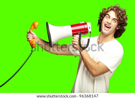 portrait of young man shouting with megaphone and talking on vintage telephone over a removable chroma key background - stock photo