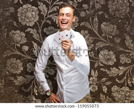 Portrait Of Young Man Showing Poker Cards On Flora Wallpaper - stock photo