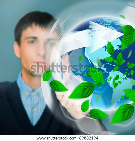 Portrait of young man sitting indoors at his office and working. Green leaves are floating around him. Business using Green power concept. - stock photo