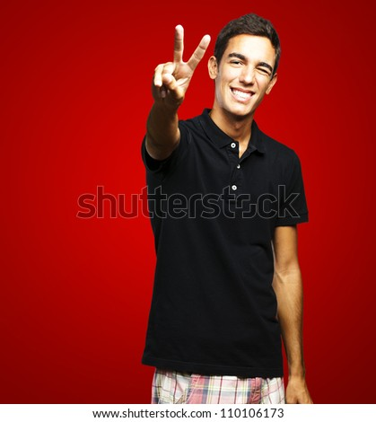 portrait of young man smiling and doing good symbol against a red background - stock photo