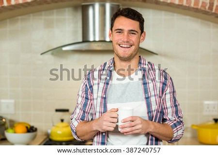 Portrait of young man smiling and holding a cup of coffee in kitchen - stock photo