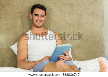 Portrait of young man smiling while using a digital tablet in bedroom - stock photo