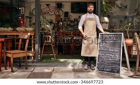 Portrait of young man standing at the entrance of his coffee shop with a black board. Barista standing in the doorway of a restaurant. - stock photo