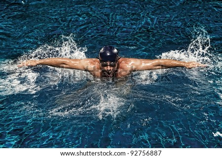 portrait of young man swimming in pool - stock photo