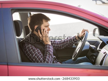 Portrait of young man talking by phone while driving a car - stock photo