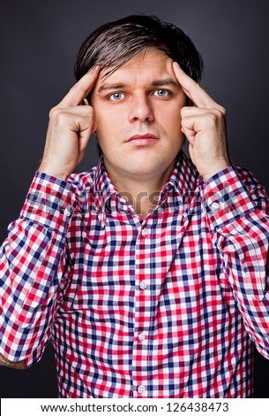 Portrait of young man  thinking hard against gray background. - stock photo