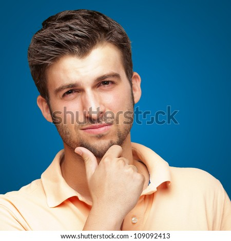 Portrait Of Young Man Touching His Chin On Blue Background - stock photo