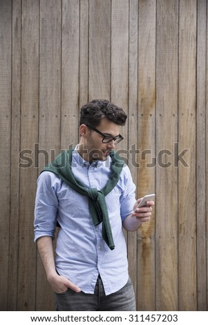 Portrait of young man using a smart phone outdoors. - stock photo