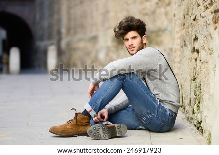 Portrait of young man wearing suspenders sitting on the floor in urban background - stock photo