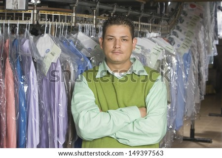 Portrait of young man with arms crossed standing in front of clothes rail - stock photo