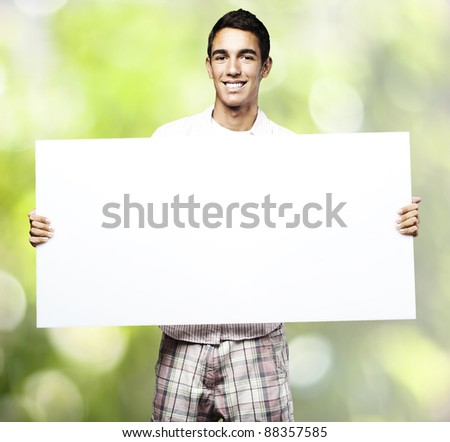 portrait of young man with banner against a plants background - stock photo