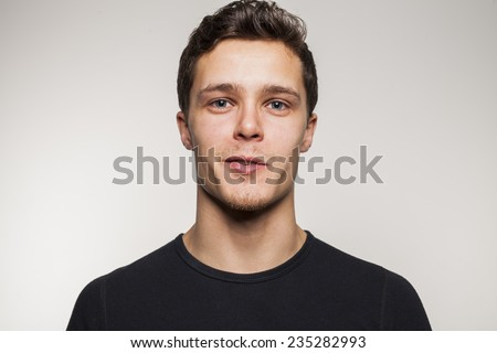 Portrait of young man with black shirt in studio setting - stock photo