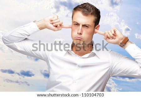 Portrait Of Young Man With Finger In His Ear, Outdoor - stock photo