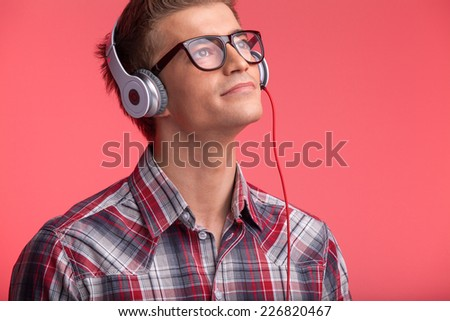 portrait of young man with glasses and headphones. guy playing music on red background - stock photo