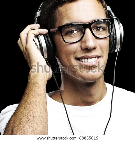 portrait of young man with glasses and headphones listening to music on a black background - stock photo
