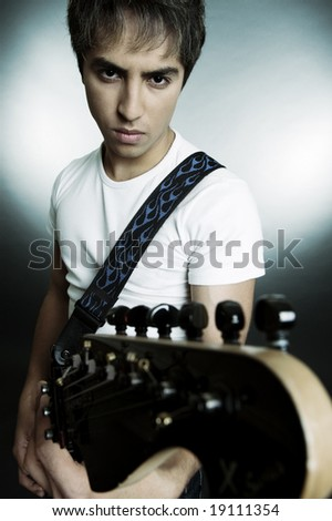 portrait of young man with guitar over grey background - stock photo