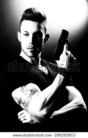 Portrait Of Young Man With Gun On Black Background - stock photo