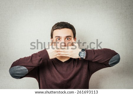 portrait of young man with hand on mouth - stock photo