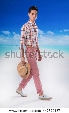 portrait of young man with hat  walking at beach background - stock photo