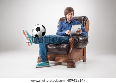 Portrait of young man with laptop and football ball - stock photo
